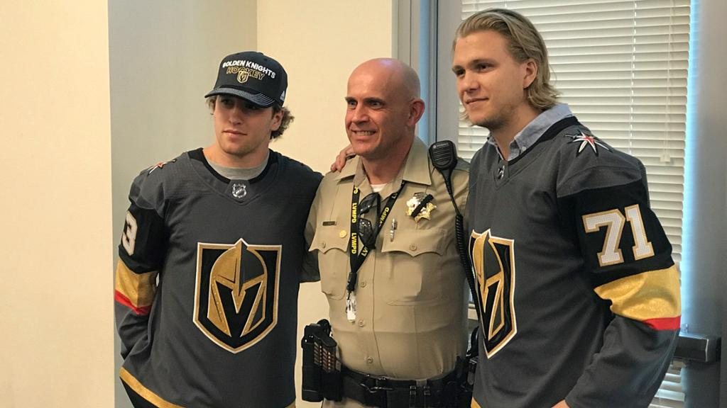 Two Vegas Golden Knights players pose with a member of the Las Vegas Metropolitan Police Department after October 1 tragedy
